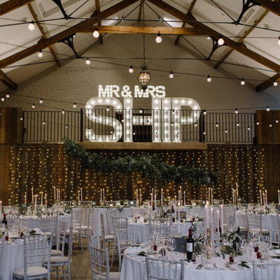 The Great barn at Oxnead Hall is adorned with fairy lights and light up letters ready for the wedding reception