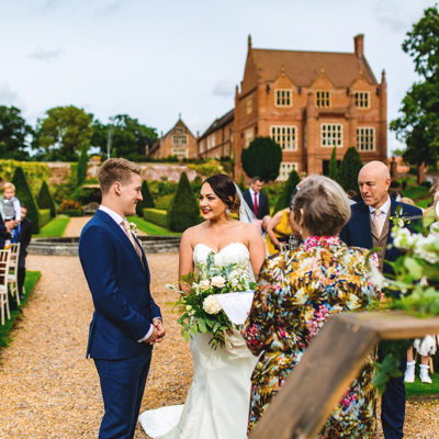 The bride and groom say their vows at their outdoor wedding in the gardens of Oxnead Hall