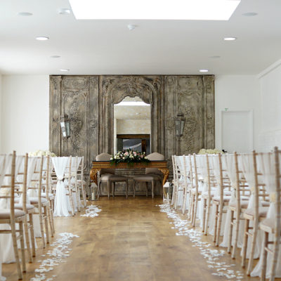 The venue was set up ready for the wedding ceremony with elegant white sashes on the chairs and white wedding flower petals lining the aisle