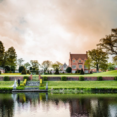 The bride and groom have a wedding photo taken alongside the water at this stunning country wedding venue